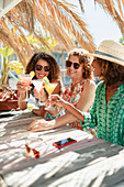 Mother and daughters drinking cocktails at beach bar