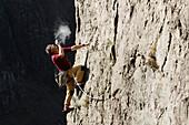 Male rock climber scaling rock face