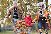 Grandparents and granddaughter kicking autumn leaves