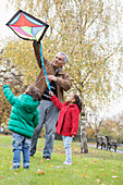 Grandfather and grandchildren flying a kite