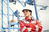 Confident female dock worker with arms crossed at shipyard