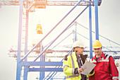 Dock worker and manager talking below crane at shipyard