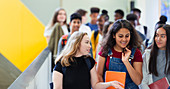 Junior high girl students walking and talking in corridor