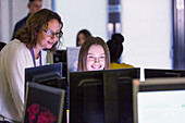 Female teacher helping student at computer in computer lab