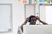 Mature student adjusting headphones at computer