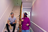 Happy couple redecorating, drinking coffee on stairs