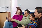 Friends taking a break from moving, using digital tablet