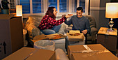 Happy couple taking a break from moving, eating pizza