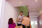 Couple moving house, carrying cardboard boxes on stairs