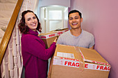 Couple moving house, carrying cardboard boxes in corridor