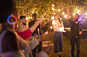 Playful friends with sparklers enjoying garden party