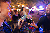 Man with credit card paying bartender at party