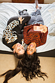 View from above teenage girl friends taking selfie on bed