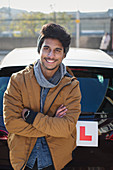 Portrait man with learners permit leaning against car