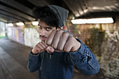 Portrait tough young man punching in urban tunnel