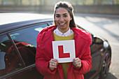 Portrait confident, woman holding learners permit by car