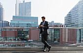 Businessman using smart phone on sunny urban balcony