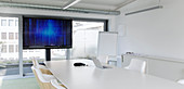 Television screen in modern conference room