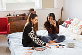 Teenage girls applying makeup, hanging out on bed
