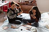Teenage girls applying makeup and brushing hair on bed
