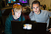Boys with headphones playing video game