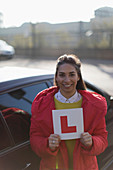 Portrait happy woman holding learner permit next to car