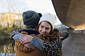 Happy young couple hugging along urban canal