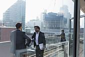Businessmen talking on highrise office balcony