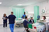 Doctors, nurses, patients and visitors in hospital ward