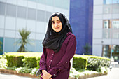 Portrait young woman in hijab outside sunny building