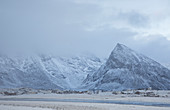 Snow covered mountains above village