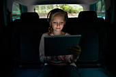 Girl with headphones and tablet in back seat of car