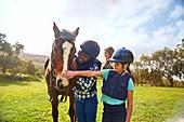 Happy girls petting horse in sunny rural paddock