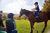 Girl learning horseback riding in rural grass paddock