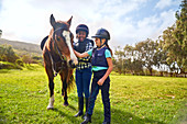Girls petting horse in sunny rural grass paddock