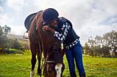 Happy girl hugging horse in rural grass paddock