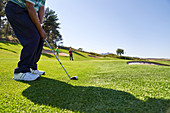 Male golfer taking a shot on sunny golf course