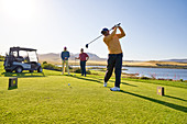Male golfer teeing off at sunny golf tee box