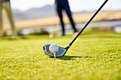 Close up golfer preparing to tee off at sunny tee box