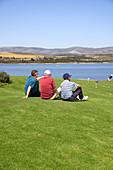 Male golfers taking a break resting in grass