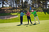 Male golfers shaking hands putting green