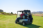 Male golfers driving golf cart on sunny golf course greens