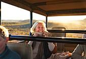 Happy senior woman on safari riding in off-road vehicle
