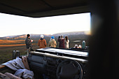 Safari group looking at landscape view outside vehicle