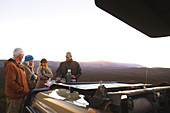 Guide and group enjoying coffee outside off-road vehicle