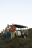 Senior couple on safari drinking tea outside vehicle
