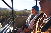 Happy senior couple riding in off-road safari vehicle