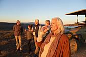 Senior woman on safari drinking champagne at sunset