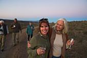 Portrait happy mature women on safari drinking champagne