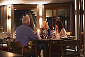 Senior friends enjoying dinner in restaurant